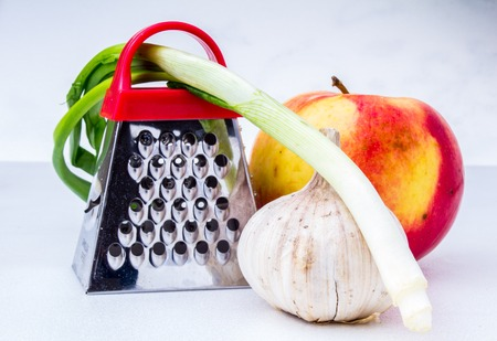 Still life: vegetables and fruits.apple, garlic, onion with small grater