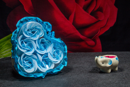 fire flower: A box with buds of blue roses and a candle-elephant on a dark background Stock Photo