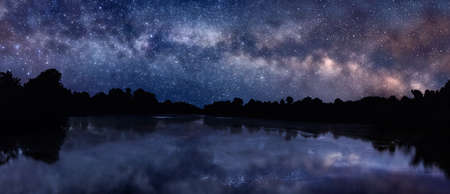 Panoramic picture of starry night sky over the lake