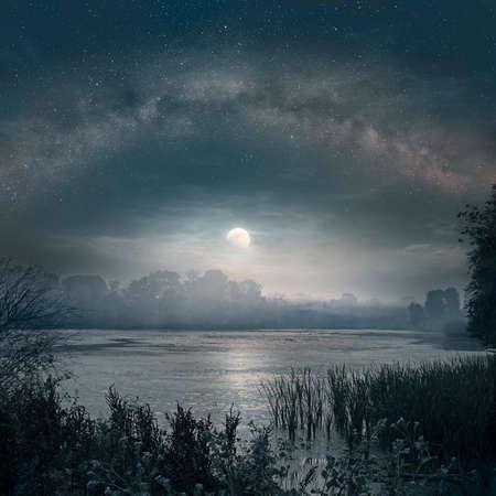 Nacht foto van de Melkweg en de stijgende Maan over het meer