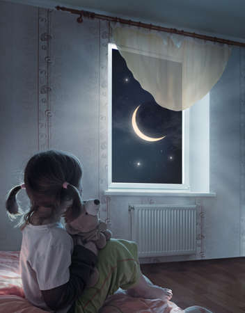 Little girl is sitting on the bed and looking at the starry sky