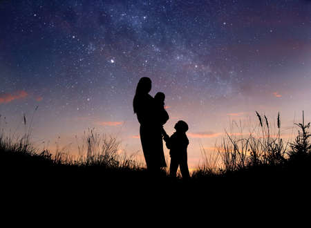 Silhouette of mother and her two little children against starry night sky 版權商用圖片