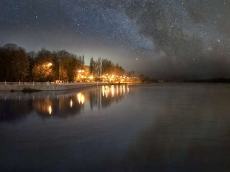 Riverside, street lights and starry sky are reflected in the river