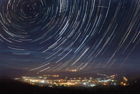 A picture of star tracks over mountain town Stock fotó