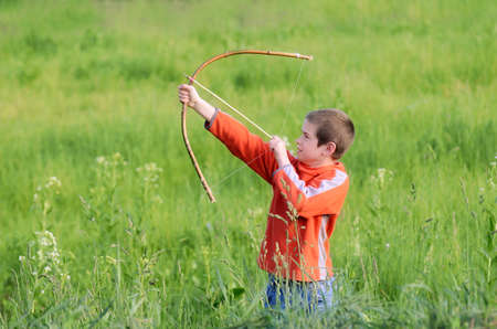 Little boy is playing with hand-made bow in the countryside