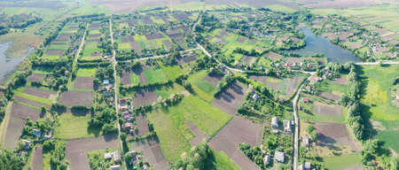 Aerial panorama of the picturesque countryside with many fields and gardens