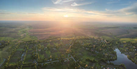 Aerial panorama of the setting sun over picturesque village Stock fotó