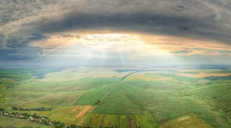 Aerial panorama of the dramatic sky with sunbeams lightening the farmland