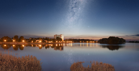 Panorama of the city quay and shining Milky Way over it