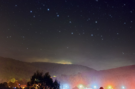 A picture of the night sky with Ursa Major constellation over the village