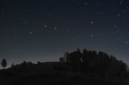 A picture of the starry night sky with Ursa Major constellation over the hill