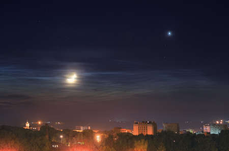 Crescent Moon and planet Venus over the night town
