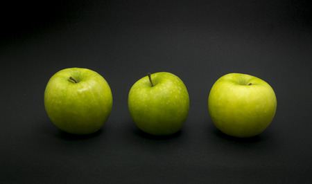 Green apples on black background. Stock Photo