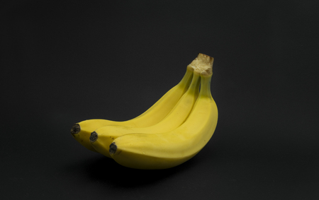 Fresh, yellow bananas on black background.