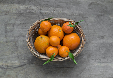 Mandarin oranges with leaves in white basket on rustic wood background.