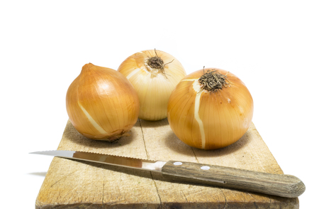 Unpeeled Onions Sit On An Isolated Chopping Board Stock Photo
