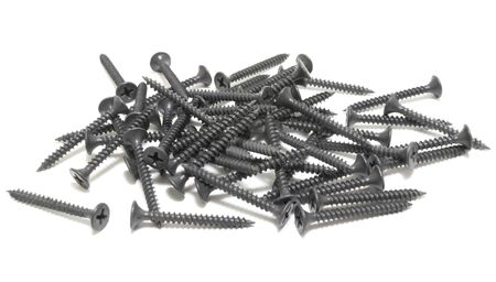 A pile of black screws. Isolated on white.
