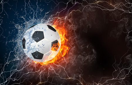 soccer equipment: Soccer ball on fire and water with lightening around on black background. Horizontal layout with text space. Stock Photo