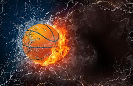 balle de basket-ball sur le feu et l'eau, avec éclairage autour sur fond noir. Disposition horizontale avec un espace de texte.