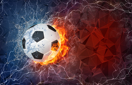 Soccer ball on fire and water with lightening around on abstract polygonal background. Horizontal layout with text space. Stock Photo