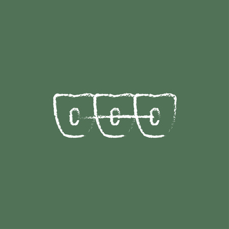 Orthodontic braces hand drawn in chalk on a blackboard vector white icon isolated on a green background. Ilustracja