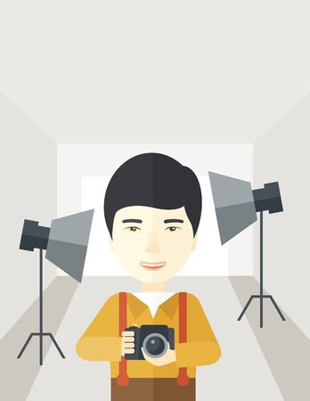 A smiling asian photographer holding a camera and standing inside the studio with the light vector flat design illustration. Vertical layout with a text space.