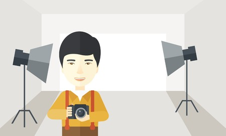 A smiling asian photographer holding a camera and standing inside the studio with the light vector flat design illustration. Horizontal layout with a text space.