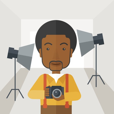A smiling african-american photographer holding a camera and standing inside the studio with the light vector flat design illustration. Square layout.