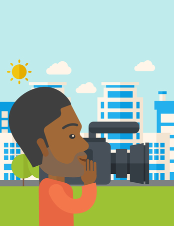 cameraman: An african-american hipster cameraman with video camera taking a video with buildings around vector flat design illustration. Vertical layout with a text space.