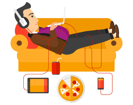 lying in: A fat man in headphones lying on a sofa with electronic devices and fast food