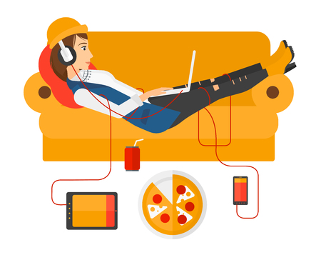 lying in: A woman in headphones lying on a sofa with electronic devices and fast food