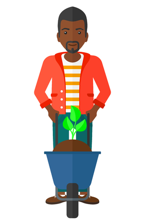 An african-american man standing with a plant and soil in a wheelbarrow vector flat design illustration isolated on white background.