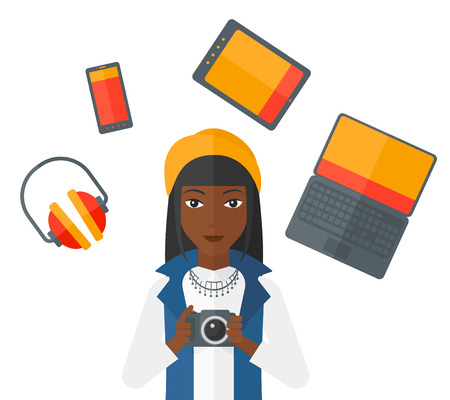 digital camera: An african-american woman holding a camera and some gadgets around her vector flat design illustration isolated on white background.