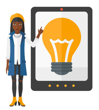 An african-american woman standing and pointing at a big tablet computer with a light bulb on a screen vector flat design illustration isolated on white background. Ilustrace