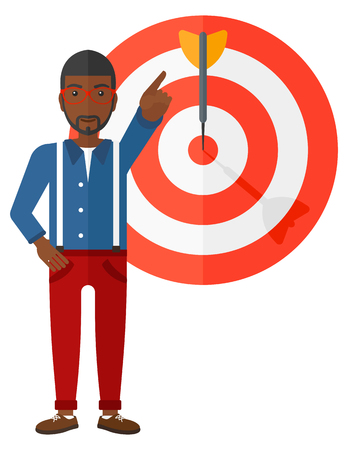 guy standing: An african-american businessman standing and pointing at arrow in a target board vector flat design illustration isolated on white background.