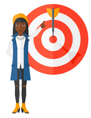 business woman standing: An african-american business woman standing and pointing at arrow in a target board vector flat design illustration isolated on white background. Illustration