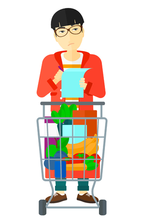 A thoughtful asian man standing with full supermarket trolley and holding a shopping list in hands vector flat design illustration isolated on white background. Illustration