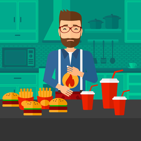 heartburn: A hipster man with the beard standing in the kitchen in front of table full of junk food and suffering from heartburn vector flat design illustration. Square layout.