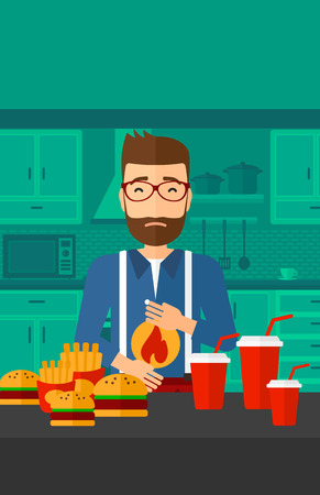 tummy: A hipster man with the beard standing in the kitchen in front of table full of junk food and suffering from heartburn vector flat design illustration. Vertical layout.