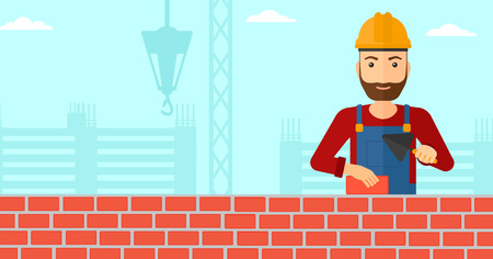 A hipster bricklayer with a spatula and a brick in hands on a background of construction site vector flat design illustration. Horizontal layout.
