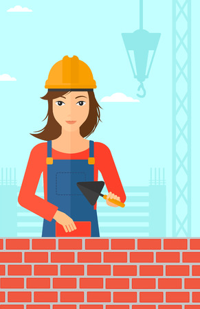 bricklayer: A female bricklayer with a spatula and a brick in hands on a background of construction site vector flat design illustration. Vertical layout.