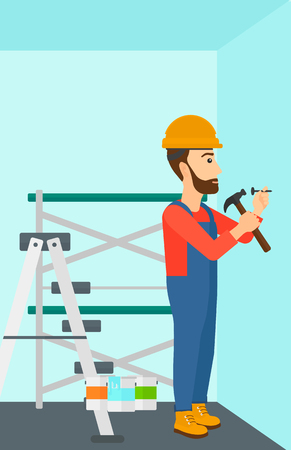 A hipster man with the beard hitting a nail in the wall with a hummer on a background of room with paint cans and ladder vector flat design illustration. Vertical layout. Иллюстрация