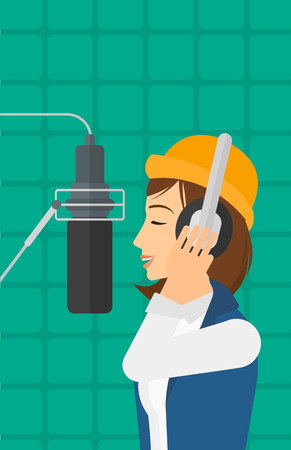 A singer in headphones making a record of her voice in studio vector flat design illustration. Vertical layout. Vettoriali