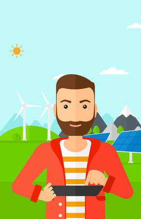 A hipster man with the beard holding a tablet computer in hands on a background with solar pannels and wind turbins vector flat design illustration. Vertical layout.