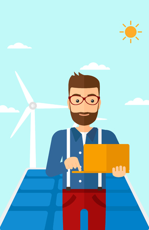 ecologically: A hipster man with the beard holding a laptop in hands on a background with solar pannels and wind turbins vector flat design illustration. Vertical layout.