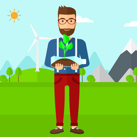 small plant: A hipster man with the beard standing on a background with wind turbins and holding in hands a plastic bottle with a small plant growing inside vector flat design illustration. Square layout. Illustration