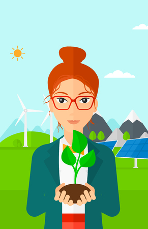 hands holding plant: Young woman holding in hands a small plant in soil on a background with solar pannels and wind turbins vector flat design illustration. Vertical layout.