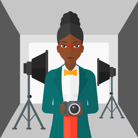 black appliances: An african-american woman holding a camera on the background of photo studio with lighting equipment vector flat design illustration. Square layout.