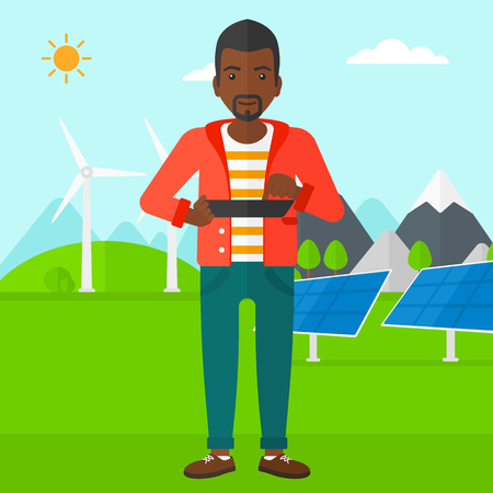 An african-american man holding a tablet computer in hands on a background with solar pannels and wind turbins vector flat design illustration. Square layout. Illusztráció