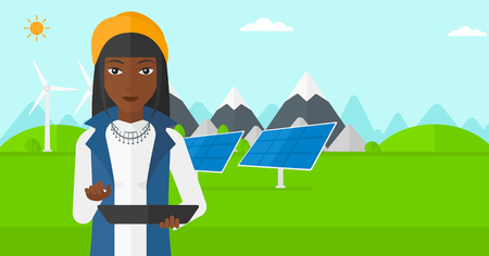An african-american woman holding a tablet computer in hands on a background with solar pannels and wind turbins vector flat design illustration. Horizontal layout.